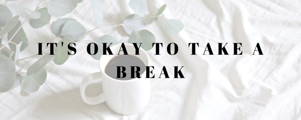 a cup of coffee and leaves on a white bed spread with a text overlay that says it's okay to take a break