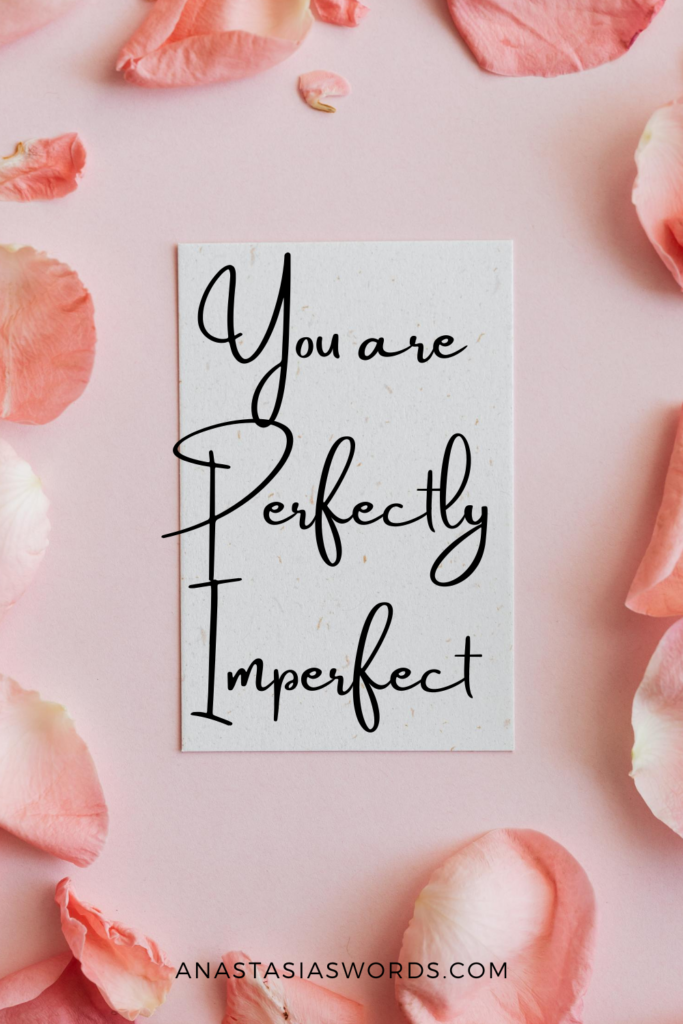 the quote 'You are perfectly imperfect' on a pice of paper that is surrounded by pink rose petals