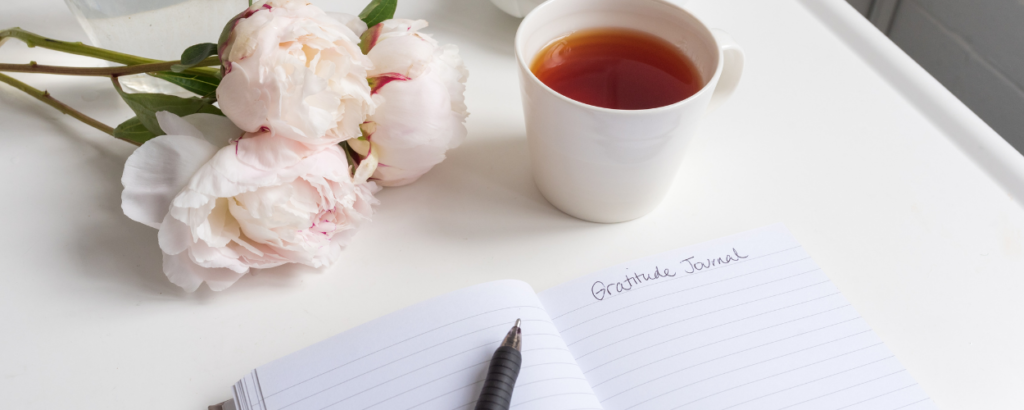 a journal, a cup of tea a pen and roses. in the journal are the words gratitude journal.