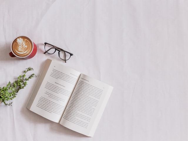 image of a book, glasses a cup of coffee and grass