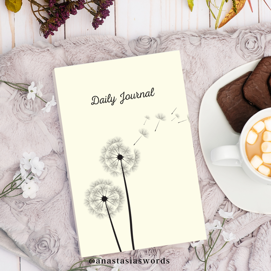 A daily journal on a table next to a plate with cookies and some flowers