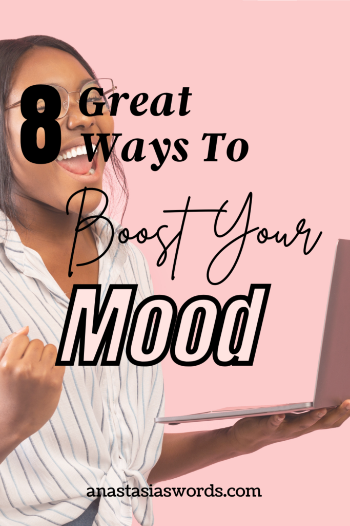 A happy woman in front of a pink background holding a laptop in her left hand. There is a text overlay that says 8 great ways to boost your mood