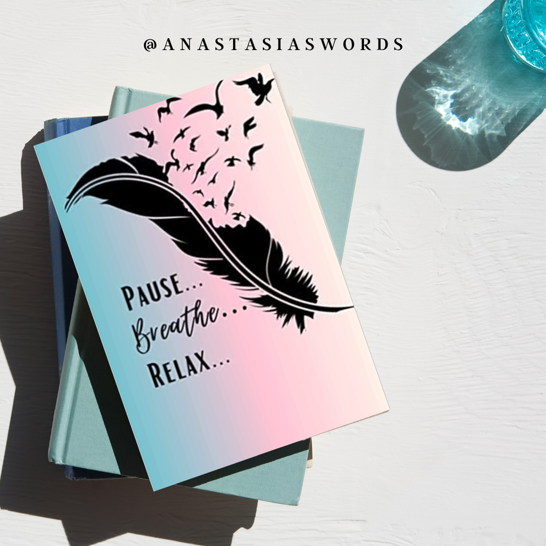 journal with a drawing of a feather and a quote that says pause breathe relax. The journal is stacked on other books and next to a cup